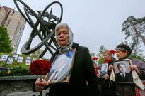 UN warns against 'complacency' on Chernobyl di... Women hold portraits of their lost husbands near a monument honoring people ...