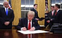 Trump signs order to withdraw from mega trade deal with Asia