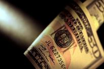 Dollar edges off lows against euro, central banks eyed