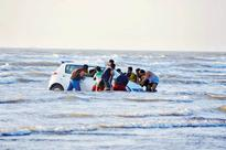 Stranded at seat: Tourists at Alibaug take their cars for a dip