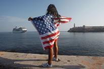 Fashion glitterati descend on Cuba for Chanel ... A woman with a U.S. flags looks at the arrival of U.S. Carnival cruise ship ...