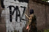 Anti-gang offensive in El Salvador cuts murder... A soldier paints over graffiti associated with the Mara Salvatrucha gang in ...