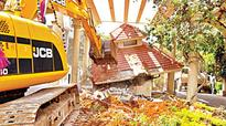 BBMP earthmovers demolish gates, wall of apartment complex