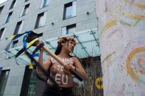 Topless female Femen protester wields sledgehammer to smash block of Berlin Wall