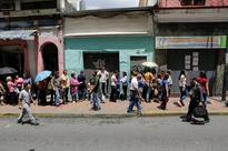 Venezuela leader hikes minimum wage 30 pct ami... People queue to try to buy basic food items outside a supermarket in Caracas...