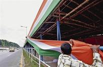 Worker holding a long Tri-colour cloth to prepare a dais at Indira Gandhi Sarani