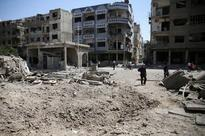 Reduced to eating grass, last hospital bombed, Assad lets besieged rebels, residents exit Damascus suburb