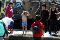 Greece to intensify evacuation of squalid migr... A child washes himself next to a watering hole in the refugees camp at the G...