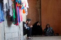 Record number of refugees need to be resettled... Syrian refugees sit inside a housing compound in Sidon, southern L...