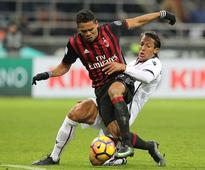 AC Milan striker Carlos Bacca (L) competes for the ball against Cagliari's Bruno Alves.