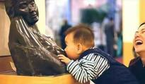 Baby mistakes a bare-breasted statue for his mother