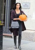 Padma Lakshmi is in Halloween spirit as she carries pumpkin while fall chic in clinging outfit with knee-high boots