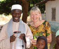 Janet Pickering introduces solar lights to village families in The Gambia