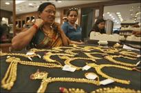 Gold prices edge down on steady dollar, firmer stocks