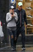 Lleyton Hewitt and wife Bec trudge through rainy Melbourne weather