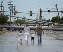 MOORE, OK - MAY 21: Downed utility poles block the road as a family walks south on Sante Fe Avenue at SW 19th Street after yesterday's deadly tornado on May 21, 2013 in Moore, Oklahoma.