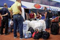 Venezuelans flood Brazil border in 36-hour gro... People stand next to bags filled with staple items and their luggage while t...