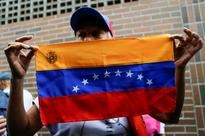 Venezuela dialogue could open way for internat... A woman holds a Venezuelan flag in Caracas, Venezuela, June 20, 2016. REUTER...