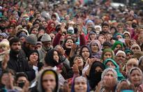 Kashmiri Muslims offer prayers as a priest displays a relic at the shrine of Sheikh Abdul Qadir Geelani in Srinagar
