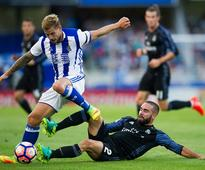 Real Sociedad defender Iñigo Martinez (L) competes for the ball against Real Madrid's Dani Carvajal.