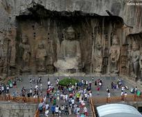Tourists visit China's Longmen Grottoes