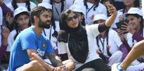 Virat Kohli sits with schoolgirls during the Save the Girl Child campaign