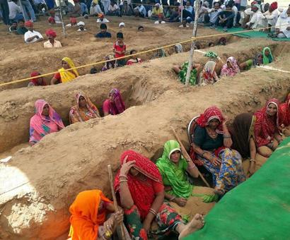Buried neck-deep in pits, farmers protest land acquisition