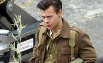Harry Styles shows off new short 'do on movie set