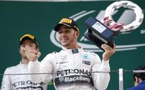 Mercedes Formula One driver Lewis Hamilton of Britain (R) gestures with his trophy as he celebrates his victory after winning the recent Chinese F1 Grand Prix at the Shanghai International Circuit.