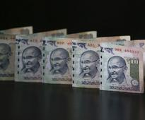 Rupee trims initial gains on dollar selling