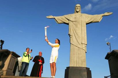 Torch begins final race to stadium from beneath Rio's Christ