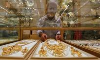Gold holds gains on weaker dollar, rising stocks cap gains