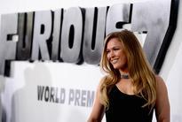 UFC fighter Ronda Rousey walks around the hou...