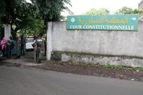Comoros court orders partial re-run of preside... People and Comorian security forces walk by the entrance of the Constitution...