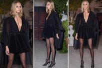Cara looks bewitching in plunging LBD, black cape and 'throat tattoo'