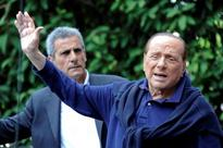 Frail-looking Berlusconi leaves hospital saying he still wants to serve
