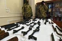 Ukraine authorities announce find of arms link... Officers of the Security Service of Ukraine stand behind a table of machine ...