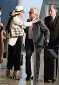 Michael Douglas greets wife Catherine Zeta-Jones with a kiss at JFK Airport