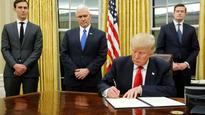 President Donald Trump in Oval Office, signs first executive order on Obamacare