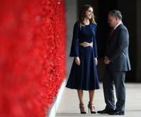 Jordan's King Abdullah II and Queen Rania walk along the wall of poppies