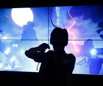 CHIBA, JAPAN - SEPTEMBER 17: A visitor wearing an HTC Corp. Vive VR headset plays a VR game in the Magical World (Beijing) Network Technology Co. booth