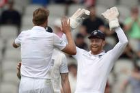 England continue to dominate at rainy Old Traf... England's Stuart Broad (L) celebrates with England's Jonathan Bairst...