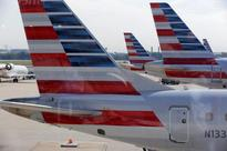 CORRECTED-American Airlines raises unit revenue forecast